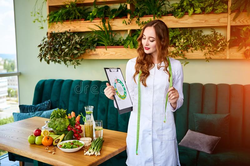 Vrouwendiëtist in medische eenvormig met meetlint die aan een dieetplan werken die zich met verschillende gezonde voedsel binnen  royalty-vrije stock fotografie