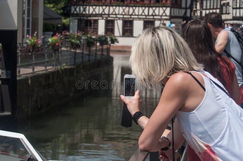 Vrouwending een beeld met telefoon bij weinig kwart van Frankrijk in Straatsburg royalty-vrije stock foto