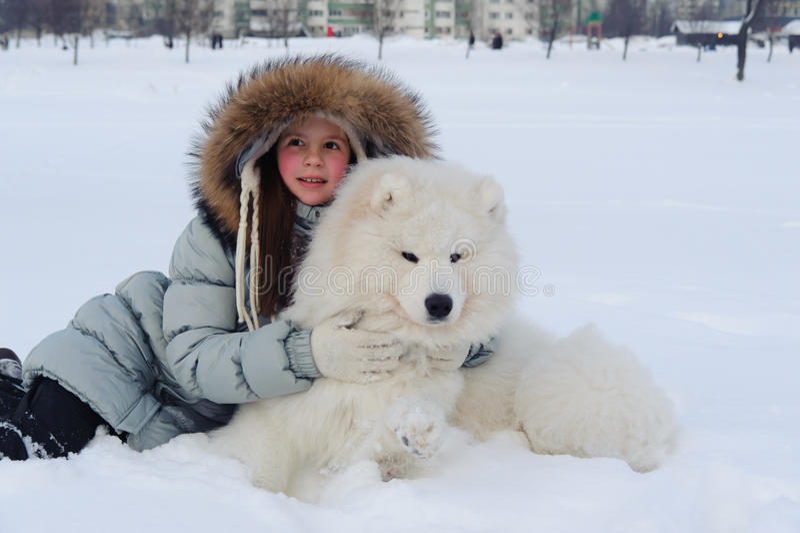 Vrouweneigenaar die witte Samoyed-hond koesteren stock foto's