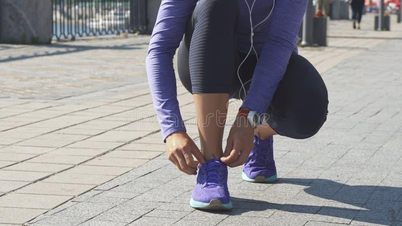 Vrouweneinden om koord op tennisschoenen te bevestigen royalty-vrije stock afbeeldingen