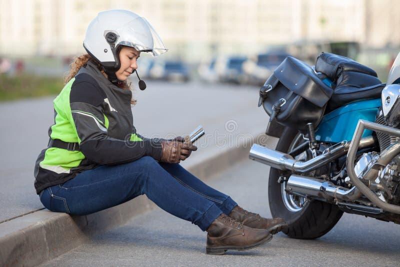 Vrouwenfietser die weg met gezeten proberen te vinden nav terwijl het zitten op kant van de weg dichtbij motorfiets royalty-vrije stock fotografie