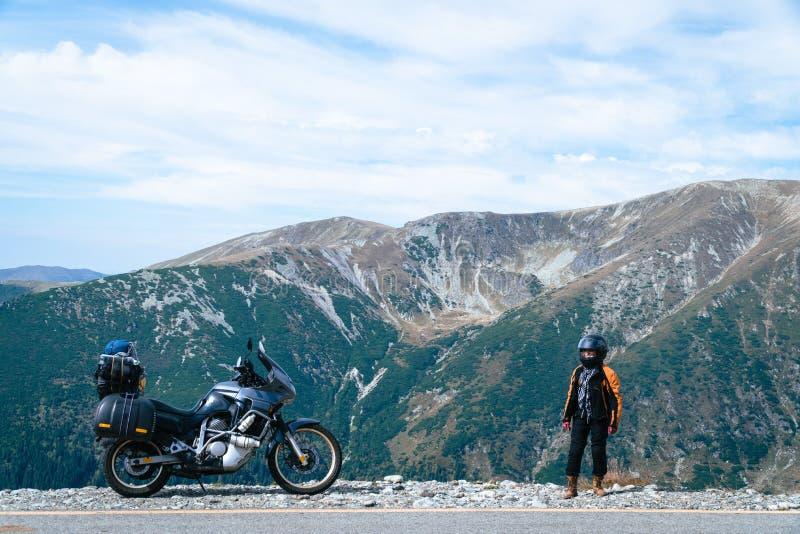 Vrouwenfietser en hoogste de bergweg van de adveturemotorfiets Reis, vakantie in Europa, motorrijdermanier, toerisme, Transalpina royalty-vrije stock afbeelding