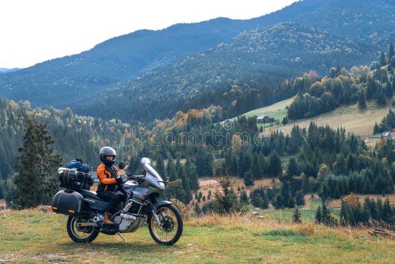 Vrouwenfietser met grote avonturenmotor, motorrijdersvakantie, wereldreiziger, lange wegreis op twee wielen De herfstdag royalty-vrije stock afbeelding