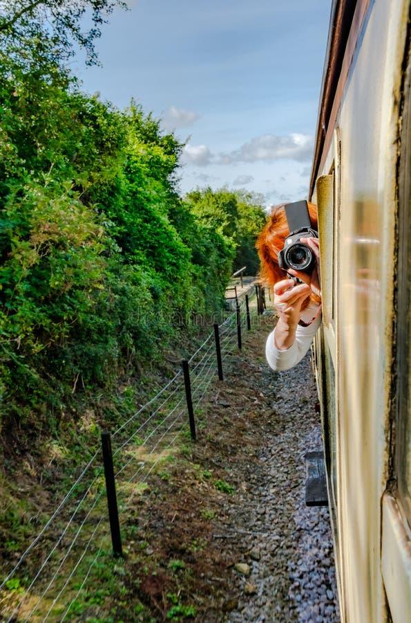 Vrouwenfotografie gezien leunend uit een bewegend venster van de passagierstrein om een foto te nemen stock foto
