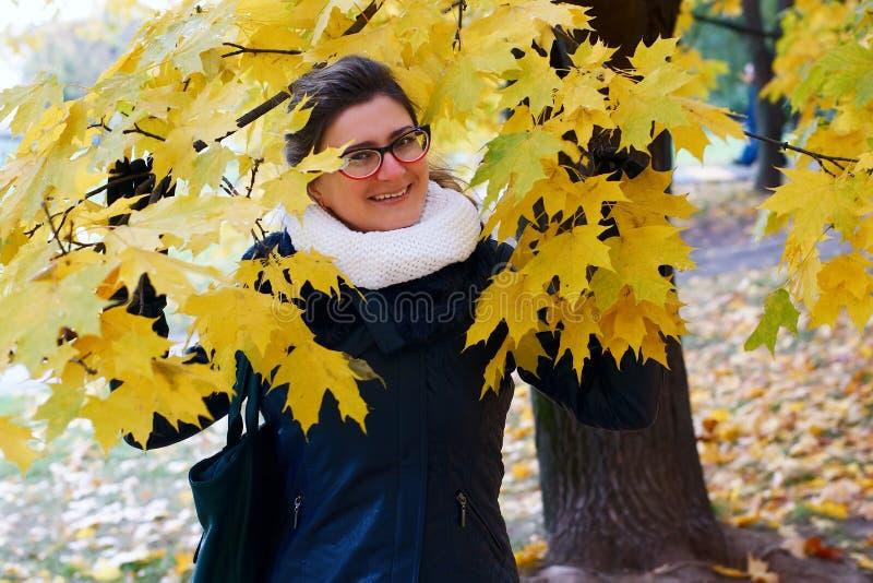Vrouwengangen in de herfstpark in een milieu van geel gebladerte stock foto's
