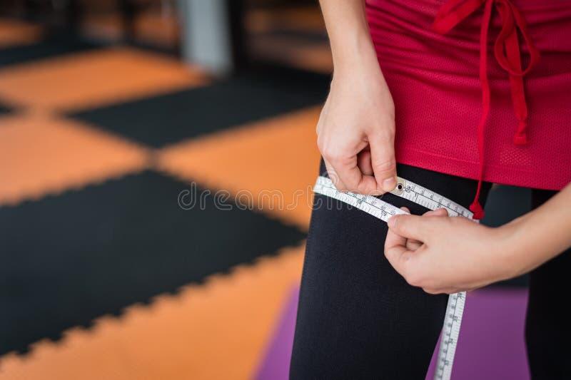 Vrouwengebruik dat band meet om haar been na oefening bij gymnastiek, concept sport en exemplaarruimte te meten stock foto