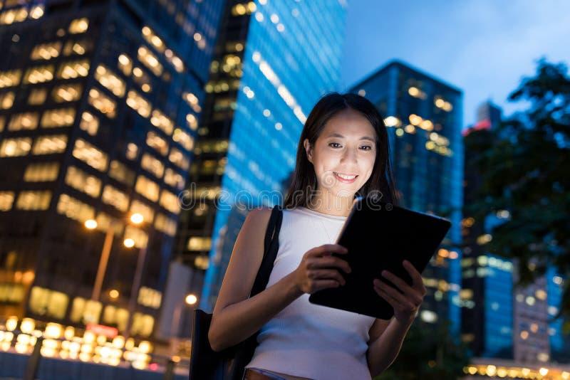 Vrouwengebruik van digitale tabletcomputer bij nacht stock afbeeldingen