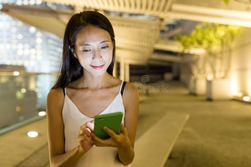 Vrouwengebruik van mobiele telefoon in stad royalty-vrije stock afbeelding