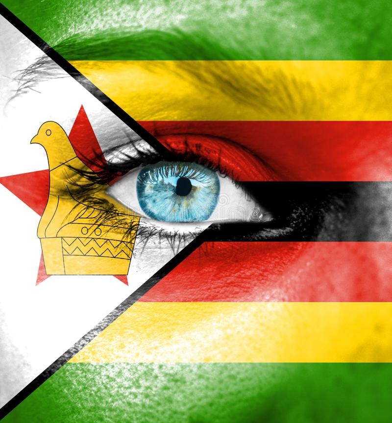 Vrouwengezicht dat met vlag van Zimbabwe wordt geschilderd stock afbeelding