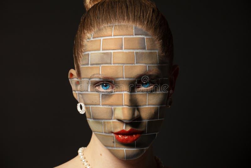 Vrouwengezicht met bakstenen muur wordt behandeld die stock afbeeldingen