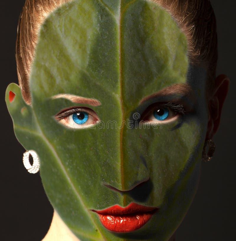 Vrouwengezicht met bladtextuur en blauwe ogen Het concept van de ecologie stock foto
