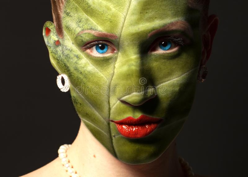 Vrouwengezicht met bladtextuur en blauwe ogen Het concept van de ecologie stock foto's