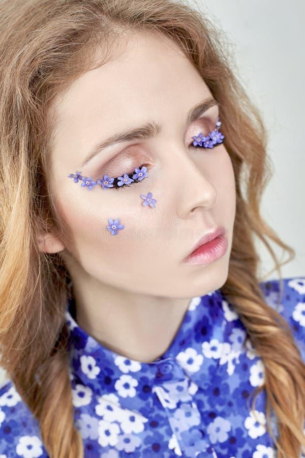 Vrouwengezicht met blauwe bloemen, het meisje in het blauw van de bloemkleding stock foto's