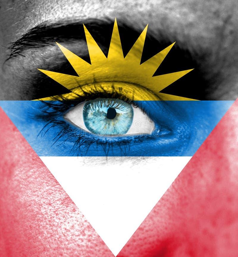 Vrouwengezicht met vlag van Antigua en Barbuda wordt geschilderd dat stock foto's