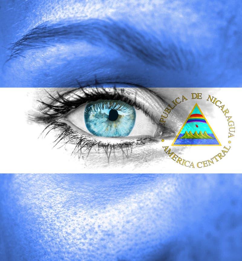 Vrouwengezicht met vlag van Nicaragua wordt geschilderd dat stock foto