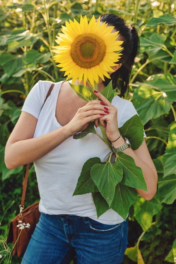 Vrouwengezicht met zonnebloem wordt behandeld die stock foto