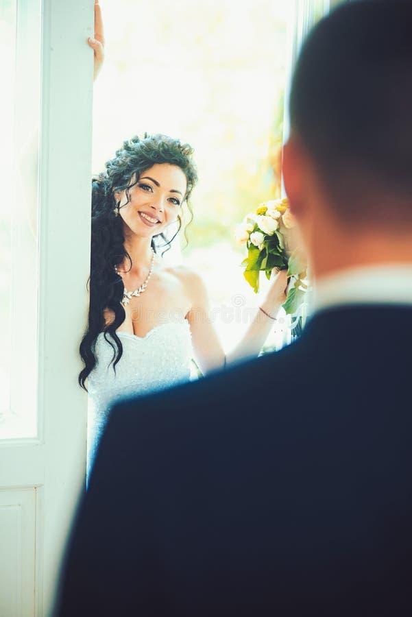 Vrouwenglimlach aan de mens op huwelijksdag Gelukkige bruid en bruidegom Sensuele vrouw met bruids make-up en kapsel Het meisje v stock afbeelding