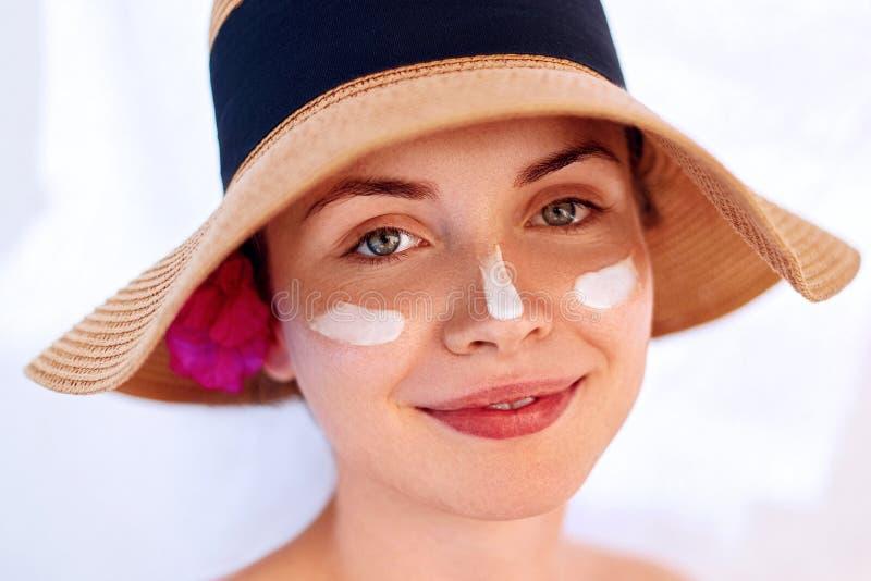 Vrouwenglimlach die zonroom op gezicht toepassen Skincare De bescherming van de lichaamszon zonnescherm Wijfje in de bevochtigend royalty-vrije stock afbeelding