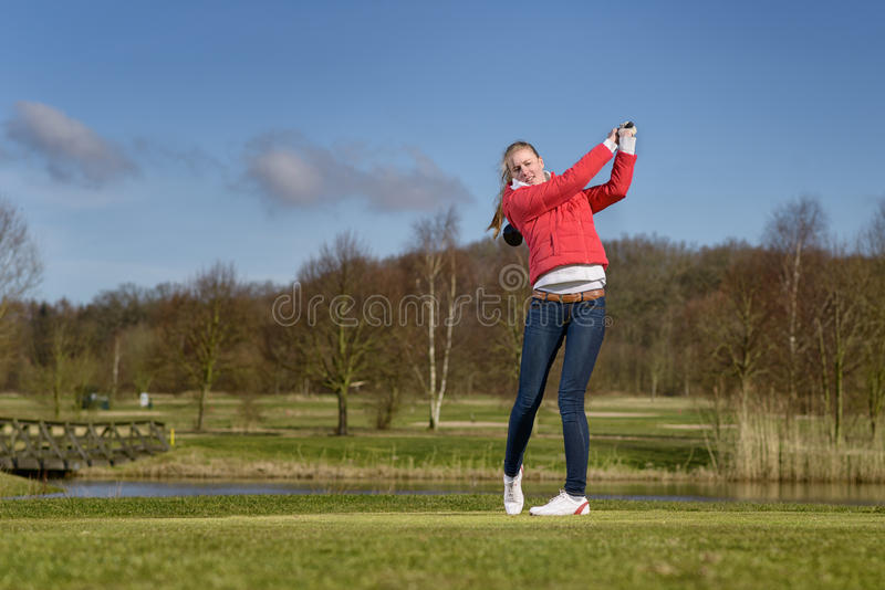 Vrouwengolfspeler die een golfbal op fairway raken royalty-vrije stock fotografie