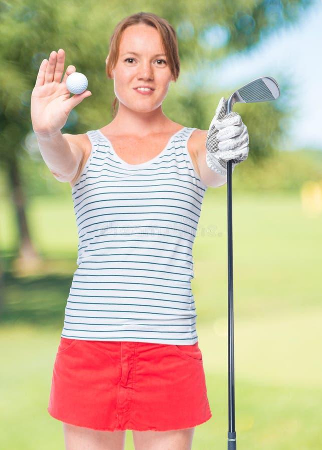 Vrouwengolfspeler een bal tonen en een golfclub, steunen die in nadruk stock foto's