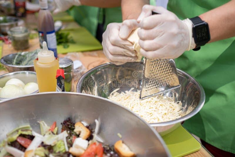 Vrouwengrating kaas op keukenlijst Het koken proc?d? stock afbeelding