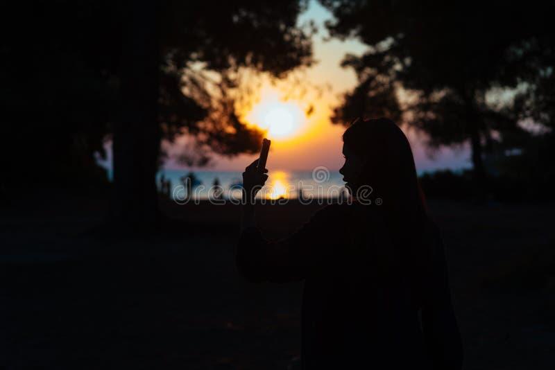 Vrouwengreep en aanrakingssmartphone over mooie zonsondergangachtergrond op zee royalty-vrije stock fotografie