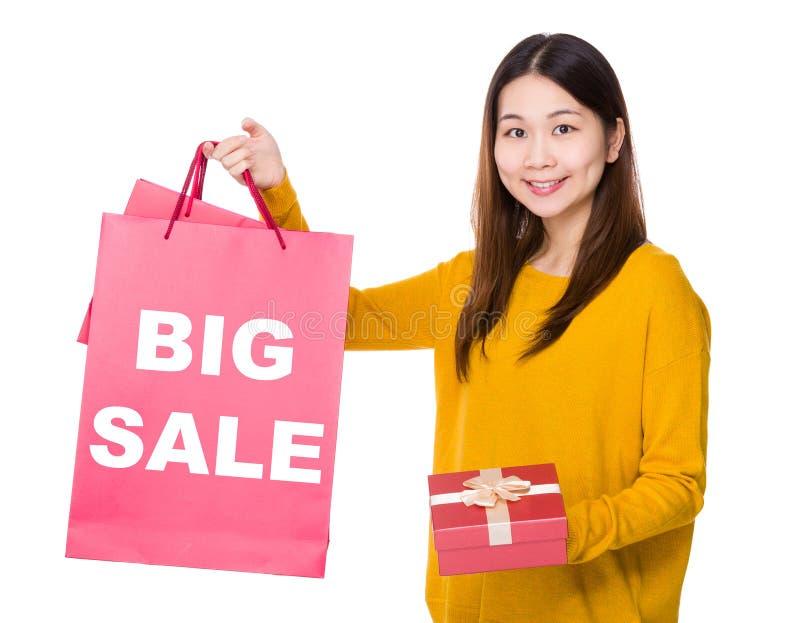 Vrouwengreep het winkelen zak en giftdoos met het tonen van grote verkoop royalty-vrije stock foto