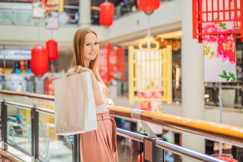 Vrouwengreep het winkelen zak tegen de achtergrond van Chinese rode lantaarns voor het Chinese Nieuwjaar Grote verkoop ter ere va royalty-vrije stock afbeelding