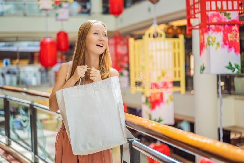 Vrouwengreep het winkelen zak tegen de achtergrond van Chinese rode lantaarns voor het Chinese Nieuwjaar Grote verkoop ter ere va stock foto's