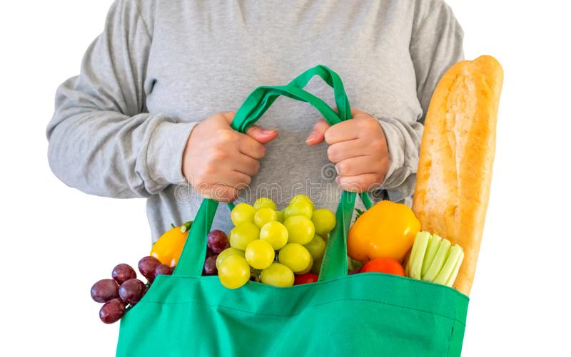 Vrouwengreep opnieuw te gebruiken die het winkelen zak met volledig verse vruchten en groentenkruidenierswinkelproduct wordt gevu royalty-vrije stock afbeeldingen