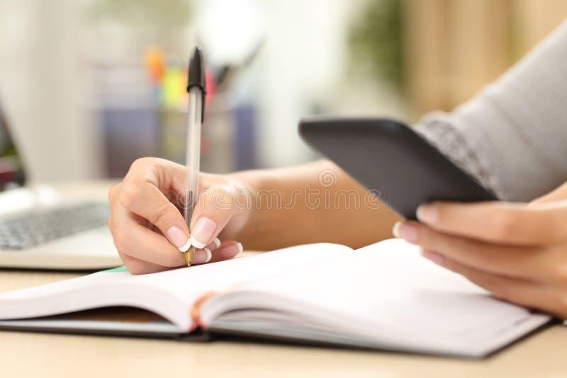 Vrouwenhand die in agenda het raadplegen telefoon schrijven stock foto's