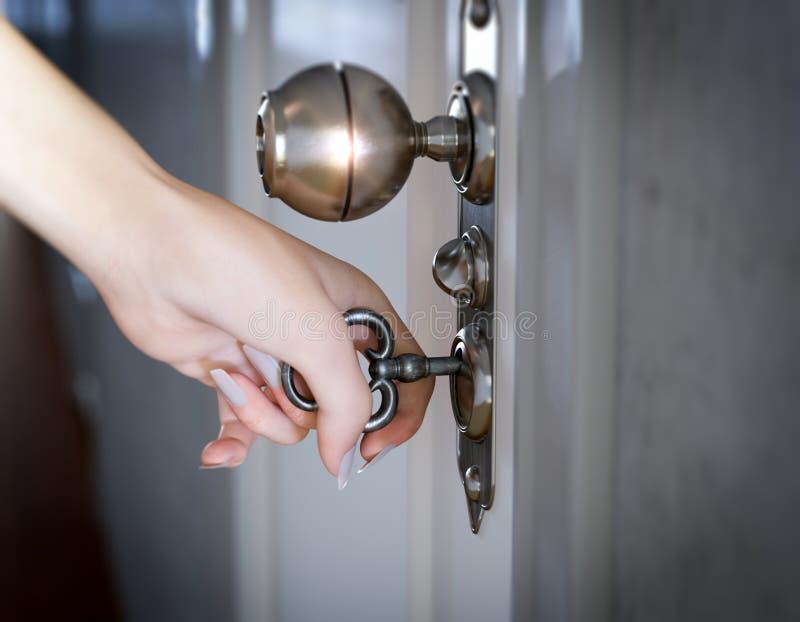 Vrouwenhand die de deur conceptuele achtergrond openen stock foto's