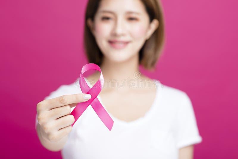 Vrouwenhand die de roze voorlichting van borstkanker tonen stock foto