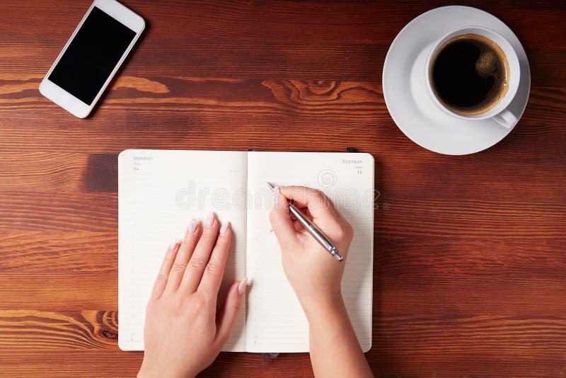 Vrouwenhand die in een agenda schrijven royalty-vrije stock foto