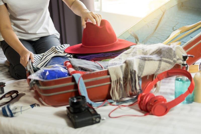 Vrouwenhand die een bagage voor een nieuwe reis en reis inpakken voor een lang weekend stock foto's