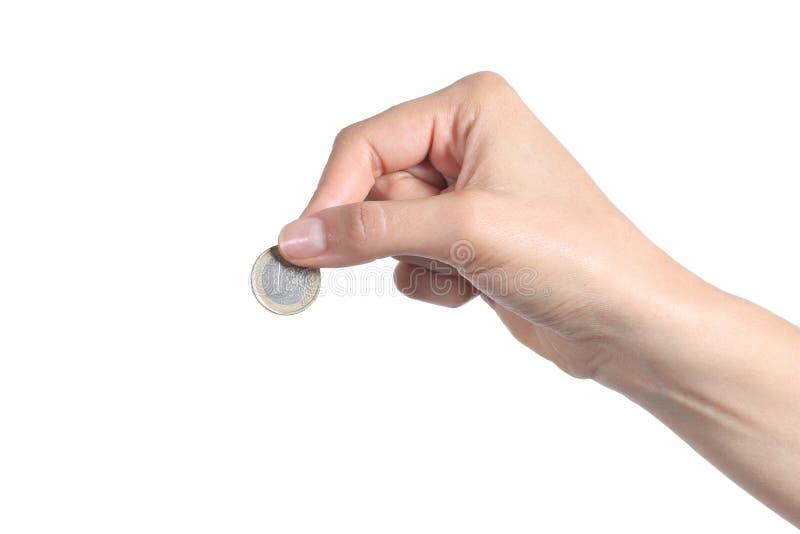 Vrouwenhand die een euro muntstuk zetten stock afbeelding