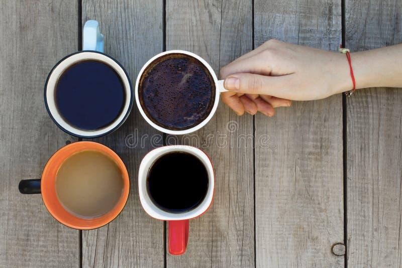 Vrouwenhand die een koffiekop op houten lijst houden stock afbeelding