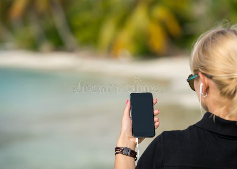 Vrouwenhand die een lege slimme telefoon op het strand met het overzees tonen stock foto's