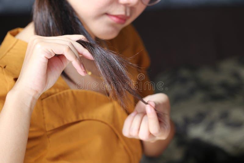 Vrouwenhand die haar lang haar met het bekijken beschadigde verdelende einden van haarverzorgingproblemen houden stock foto's