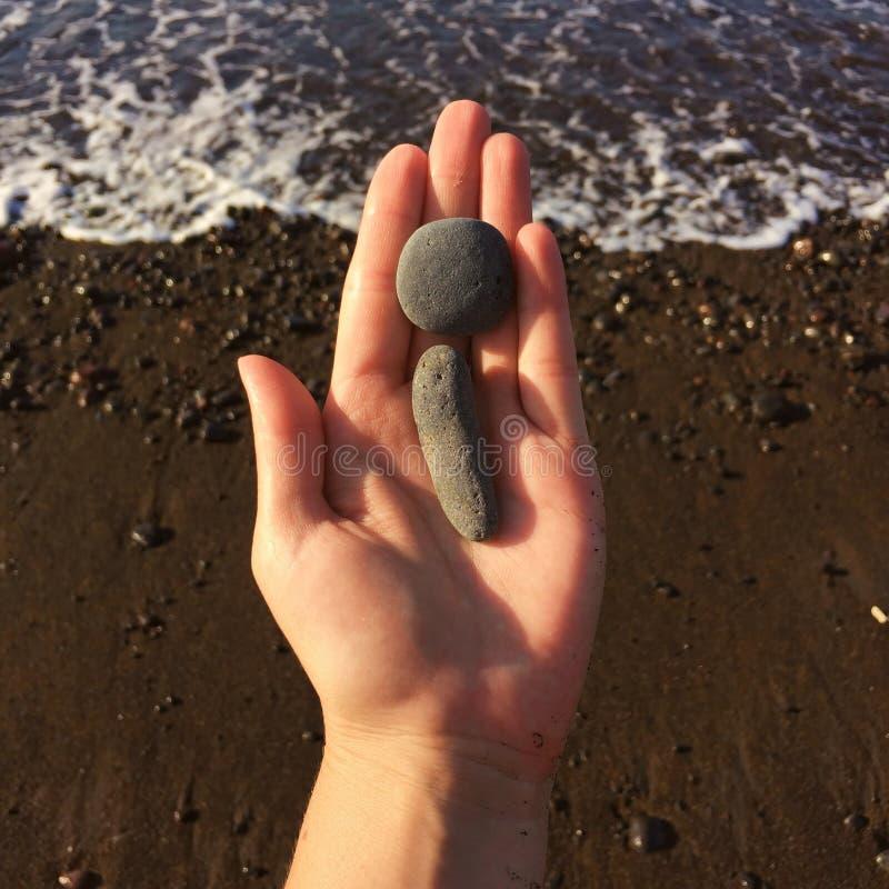 Vrouwenhand die kleine stenen in hand dichtbijgelegen blauwe overzees op een strandachtergrond houden royalty-vrije stock fotografie