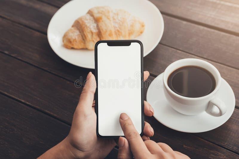 Vrouwenhand die lege smartphone met behulp van tijdens ontbijt royalty-vrije stock afbeelding