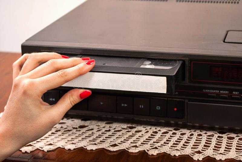 Vrouwenhand die lege VHS-cassette opnemen in oude videorecorder stock foto