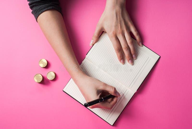 Vrouwenhand die met een pen in een notitieboekje en muntstuk op roze achtergrond schrijven stock foto
