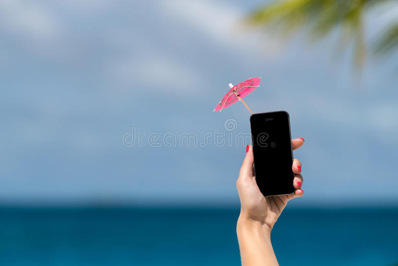 Vrouwenhand die mobiele telefoon en cocktailparaplu op de hemel tonen stock fotografie