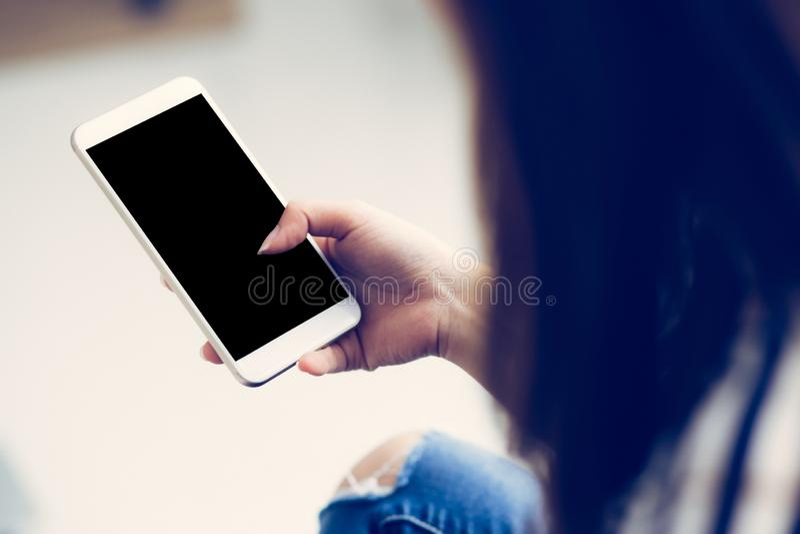 Vrouwenhand die slimme mobiele telefoon met bericht of e-mail, de telefoon van de meisjescel met exemplaarruimte houden voor inho stock foto