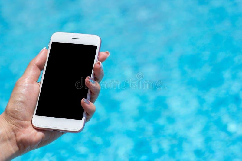 Vrouwenhand die smartphone dichtbij zwembad, close-up gebruiken stock afbeeldingen