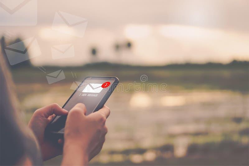 Vrouwenhand die smartphone gebruiken om e-mail te verzenden en te ontvangen stock foto