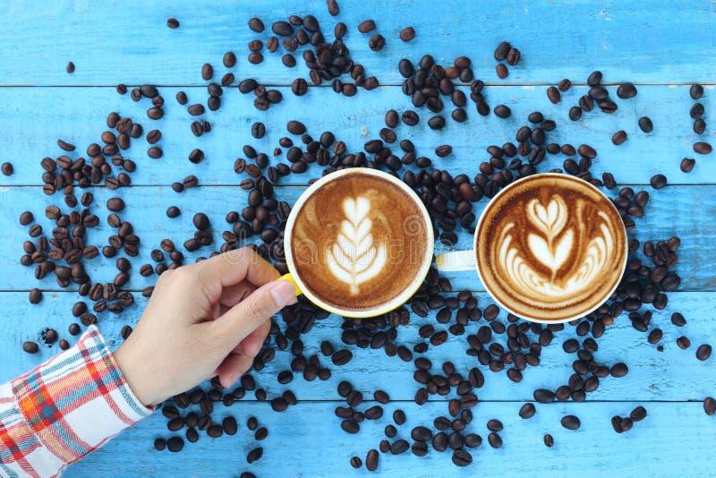 Vrouwenhand die twee koppen van lattekunst houden met patroon de bladeren royalty-vrije stock afbeeldingen