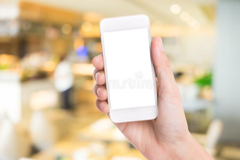 Vrouwenhand die witte smartphone op vage achtergrond houden bij sho stock foto