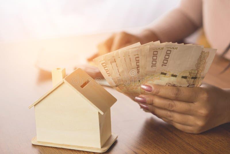 Vrouwenhand het berekenen geld met huismodel bij het houten lijst schaven om huis te kopen of te huren stock foto
